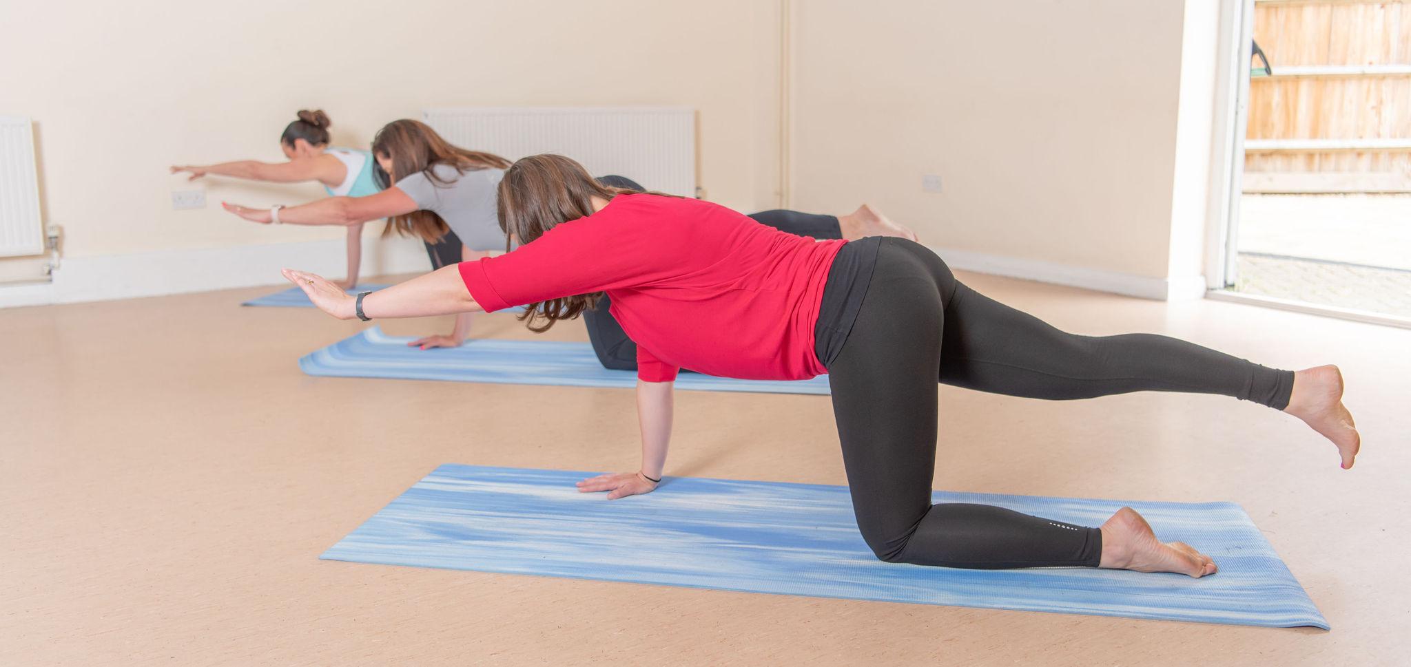 3 women extending arm and leg