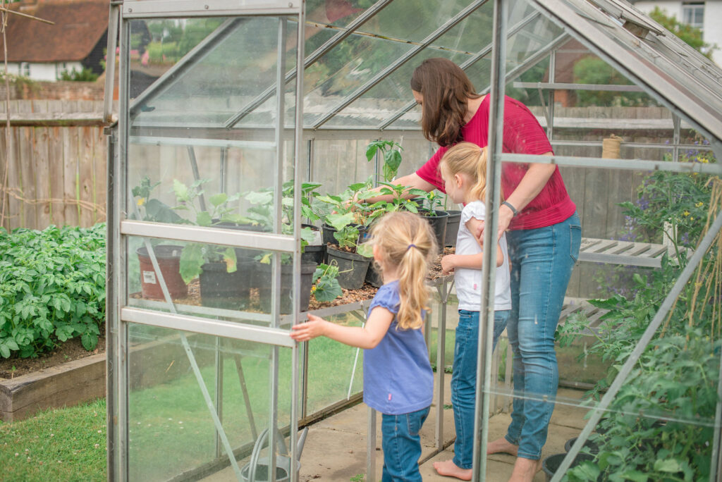 Emma and children look at the plants in the greenhouse.
